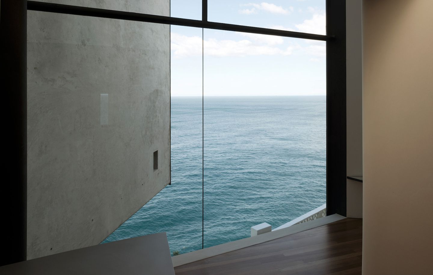 View of ocean and horizon through frameless glass at cliff front house at Dover Heights Sydney designed by Durbach Block Jaggers Architects