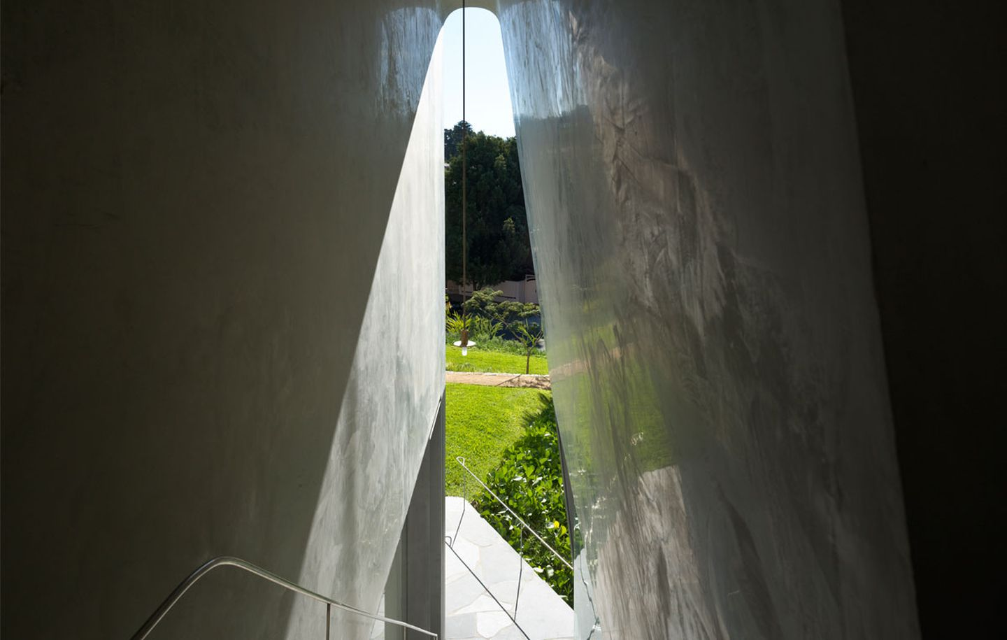 Polished plaster arch framing view of garden at family house in Dover Heights Sydney designed by Durbach Block Jaggers Architects