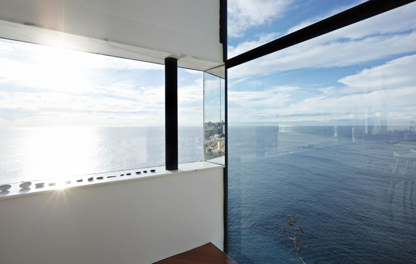 Dark grey steel and Carrara marble window looking out over cliff in house at Dover Heights Sydney designed by Durbach Block Jaggers Architects