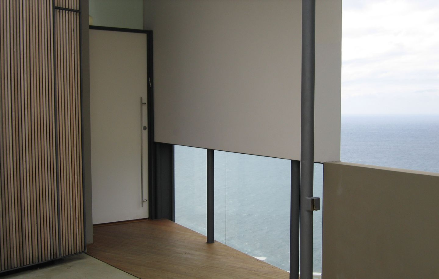 White painted entry door with frameless glass framing view of ocean in cliff house in Dover Heights Sydney designed by Durbach Block Jaggers Architects